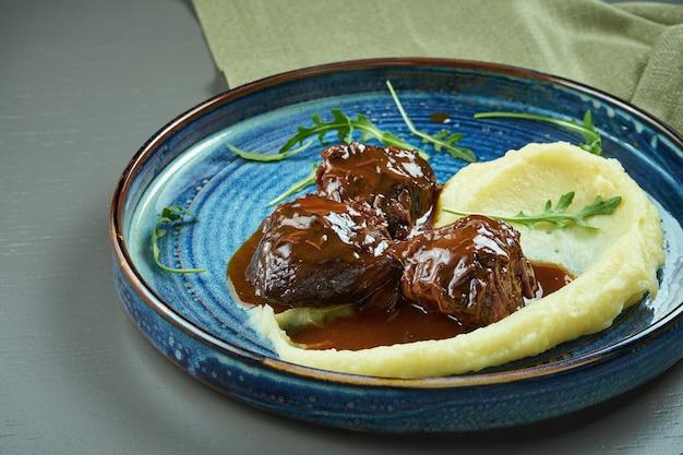木製のテーブルのブループレートに蜂蜜ソースとマッシュドガーニッシュのおいしい子牛の頬。セレクティブフォーカス