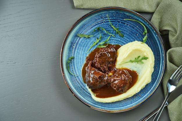 木製のテーブルのブループレートに蜂蜜ソースとマッシュドガーニッシュのおいしい子牛の頬。コピースペースの平面図
