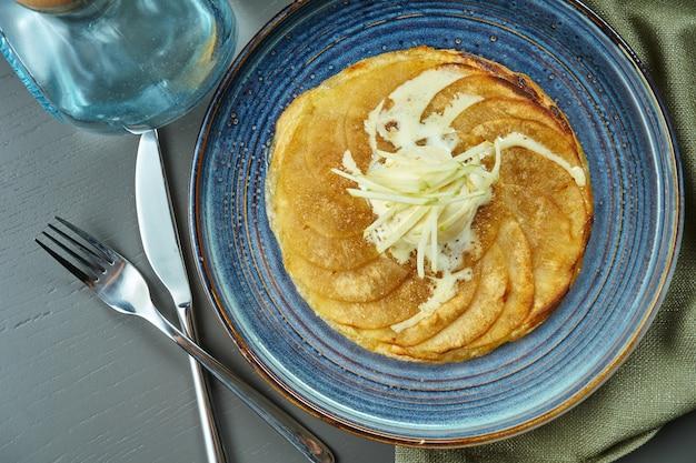 Яблочный штрудель с ванильным мороженым на синюю тарелку на деревянном столе. популярная австрийская выпечка и десерт. вид сверху, плоская планировка с копией пространства