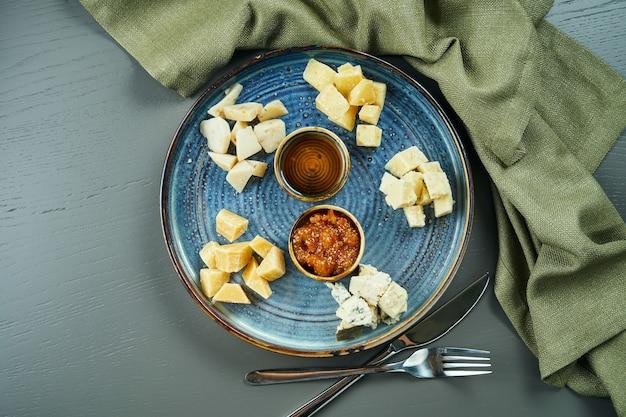 前菜-チーズプレート。セラミックプレートの異なる自家製チーズ-ブリー、カマンベール、蜂蜜とナッツを使ったオランダ料理。ワイン前菜。トップビュー、フラットレイアウト、コピースペース