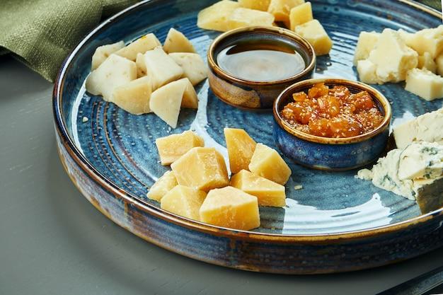 前菜-チーズプレート。セラミックプレートの異なる自家製チーズ-ブリー、カマンベール、蜂蜜とナッツを使ったオランダ料理。ワイン前菜。クローズアップ、セレクティブフォーカス