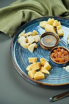 前菜-チーズプレート。セラミックプレートの異なる自家製チーズ-ブリー、カマンベール、蜂蜜とナッツを使ったオランダ料理。ワイン前菜。クローズアップ、セレクティブフォーカス、垂直