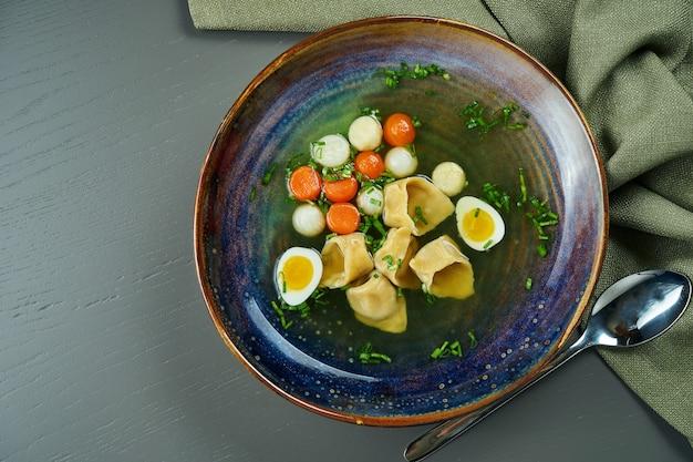 木製の表面の青いボウルにラビオリと茹でた野菜の食欲をそそるチキンスープ。ランチはイタリア料理。トップビュー、コピースペースフラットレイアウト