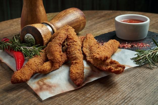 Отличная закуска к пиву - это набор фрикадельки из куриного наггетса с пергаментным соусом на каменном подносе. еда в пабе. крупным планом, селективный фокус