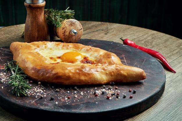 Крупным планом на вкусный традиционный аджарский хачапури - открытый запеченный пирог с сыром (сулугуни) и яичным желтком на деревянном подносе. традиционная грузинская еда