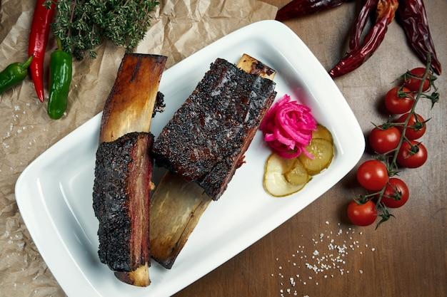 食欲をそそる美味しいスモークとグリルしたカルビの上面図。バーベキューリブ-白い皿にアメリカ料理の古典的な料理。木製テーブル
