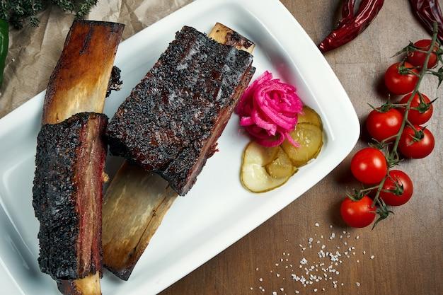 食欲をそそる美味しいスモークとグリルしたカルビの上面図。バーベキューリブ-白い皿にアメリカ料理の古典的な料理。閉じる