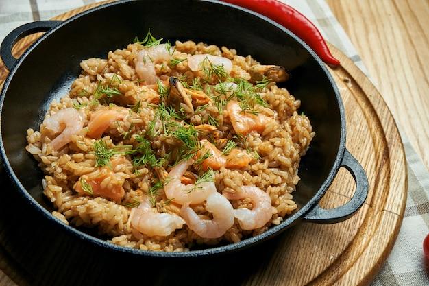 パッドタイまたはファッドタイ-古典的なタイ料理中華鍋の中華炒め麺とエビと野菜の木製テーブルの上の黒い皿。閉じる