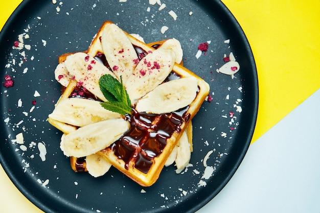 ベルギーワッフル、チョコレート、バナナ、アーモンドを色付きの面に黒い皿の上に食欲をそそる甘いペストリー。朝食用食品