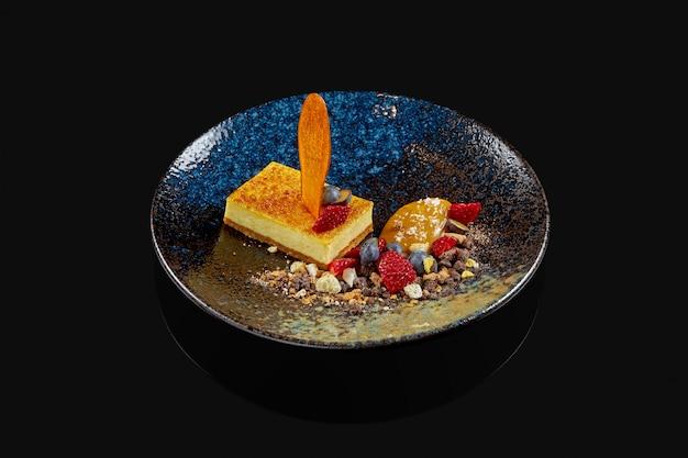 伝統的なニューヨークのチーズケーキ。ブルーベリー、イチゴ、キャラメル化した洋ナシと黒いセラミックプレート。スタイリッシュなレストラン。デザート