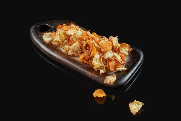 木製トレイの食欲をそそる野菜チップ。黒い表面にポテト、キノコ、ニンジンのチップ。ビールのおやつ。メニューの写真