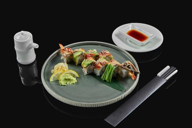 Аппетитные суши роллы дракон с авокадо, копченым угрем и креветками в черной керамической тарелке с палочками для еды и соевым соусом. черная поверхность традиционная японская еда