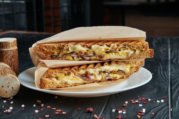 Аппетитный вегетарианский клуб-сэндвич в тостовом хлебе с плавленым сыром, красным луком, грибами в крафт-бумаге на черном деревянном.