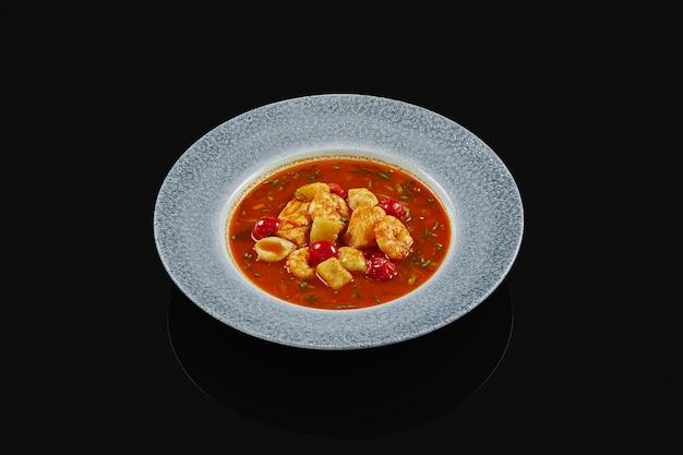 Классический испанский томатный суп с морепродуктами в серый, керамическая тарелка на черной поверхности. красный суп с креветками, лососем и морскими гребешками. фото еды для меню