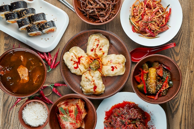 伝統的な韓国料理の盛り合わせ-キムチ、キンバップロール、木の表面で蒸した餃子(マンドゥ)。平面図、フラットレイアウトの食品。韓国料理