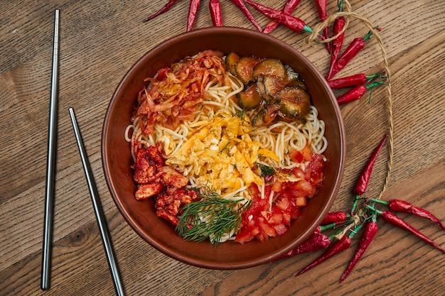 Традиционная корейская вок-лапша с острым перцем, мясом, грибами шиитаке и омлетом в керамической тарелке на деревянной поверхности. вид сверху еды