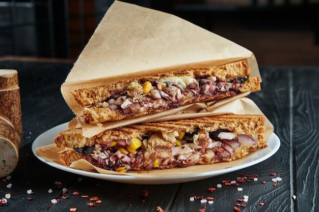 Аппетитный вегетарианский клубный бутерброд в тостовом хлебе с красным луком, кукурузой, капустой и соусом терияки в крафт-бумаге на черном деревянном. закрыть