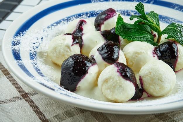 伝統的なウクライナの怠惰な餃子。ベリージャムと白い木製のテーブルの白いプレートにカッテージチーズの餃子。美味しくて甘い朝食。ヴァレニキ