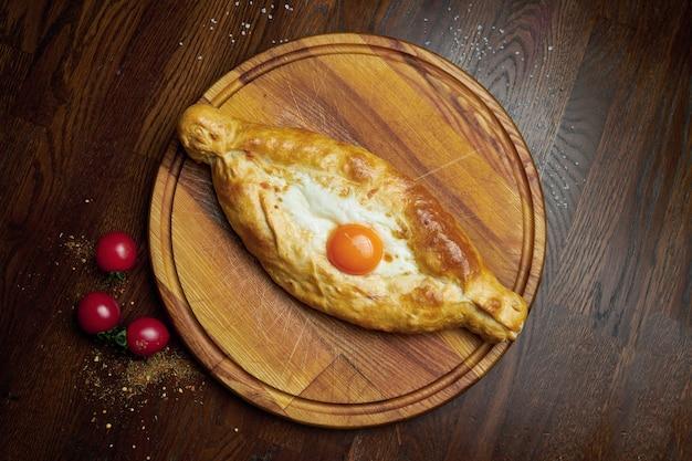 おいしい伝統的なアジャリアンハチャプリ-溶かした塩チーズ(スルグニ)と木製のトレイに卵の黄身を開いた焼きたてパイの平面図。伝統的なグルジア料理