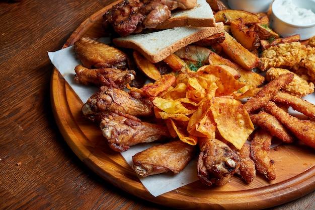 Отличная закуска к пиву - это набор фрикадельки из куриного наггетса с пергаментным соусом на каменном подносе. еда в пабе. закройте