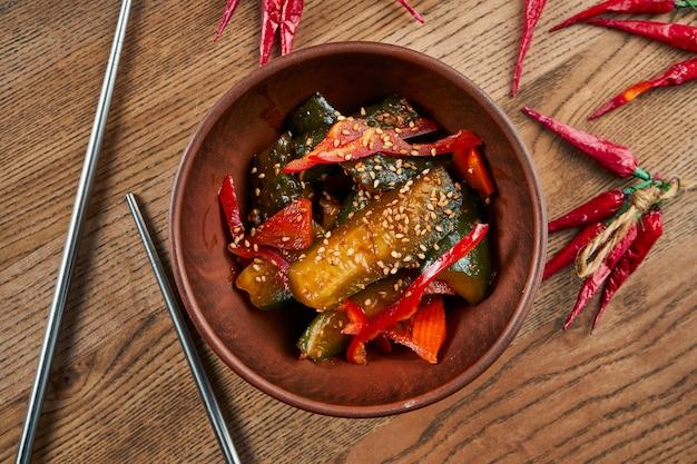 セラミックブラウンボウルに唐辛子と伝統的なアジア(韓国)打たれた(漬けた)キュウリのサラダの平面図。おいしい食べ物