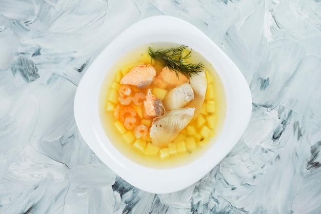 灰色のテーブルの上の白いボウルにスズキ、サーモン、エビと自家製の透明な魚のスープ。シーフード