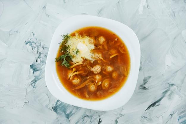 Итальянский суп с макаронами и телятиной россини с маслом в миску белого на сером столе.