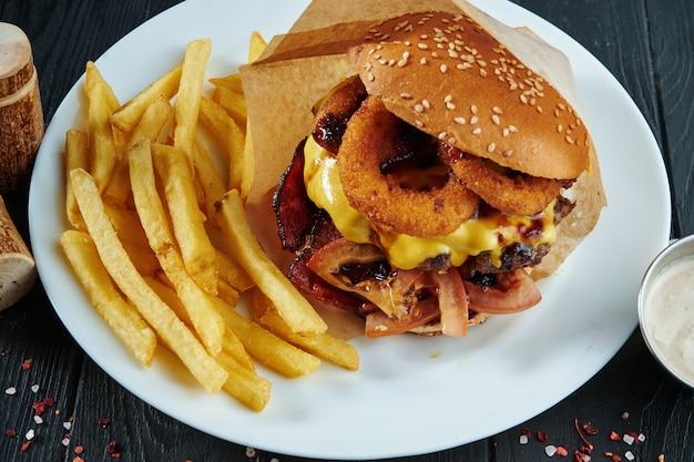 Аппетитный и сочный бургер с жареным луком, плавленым сыром, помидорами и котлетой из говядины на белой тарелке с картофелем фри. вид сверху, выборочный фокус