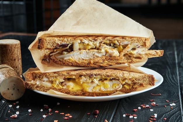 Аппетитный клубный бутерброд в тостовом хлебе с плавленым сыром, курицей, капустой и луком в крафт-бумаге на черной деревянной поверхности