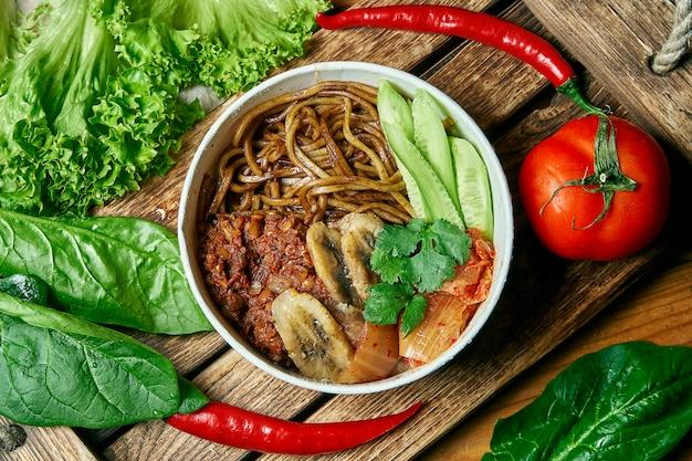 そば粉麺、揚げバナナ、きゅうり、キムチ、新鮮な野菜のコンポジションの木製トレイのベジタリアンボウル。