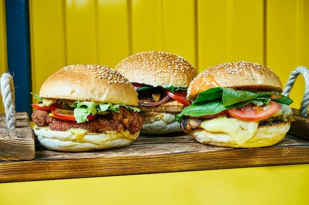 Три сочных бургера с плавленым сыром с мясным пирожком на крафт-бумаге. желтый стол. улица, фастфуд. закрыть вверх ..