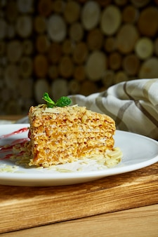 Кусок вафельный торт, пропитанный сгущенным молоком на белой тарелке. вкусный десерт из россии