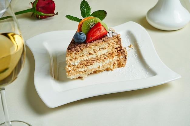 白いプレート上の有名な伝統的なキエフケーキ(ヘーゼルナッツのダコイズケーキ)。美味しいメレンゲレイヤーとバニラバタークリームのデザート。食品フラットレイ