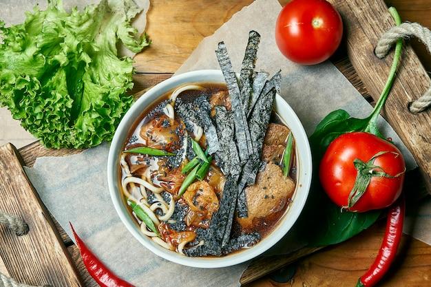 新鮮な野菜のコンポジションで木製トレイにラーメンスープ、しいたけ、大豆肉のベジタリアンボウル。健康食品。
