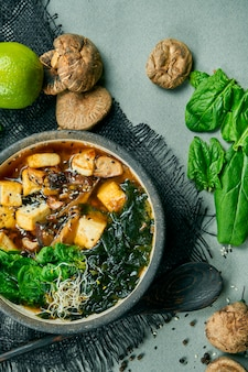 しいたけ、豆腐チーズ、海苔をグレーの布にのせた新鮮なベジタリアンみそ汁。健康的でバランスの取れた料理。上面図。