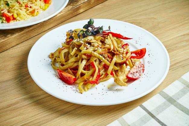 トマト、ピーマン、チキンのパスタ。木製のテーブルの白いプレートに肉と野菜の麺。閉じる