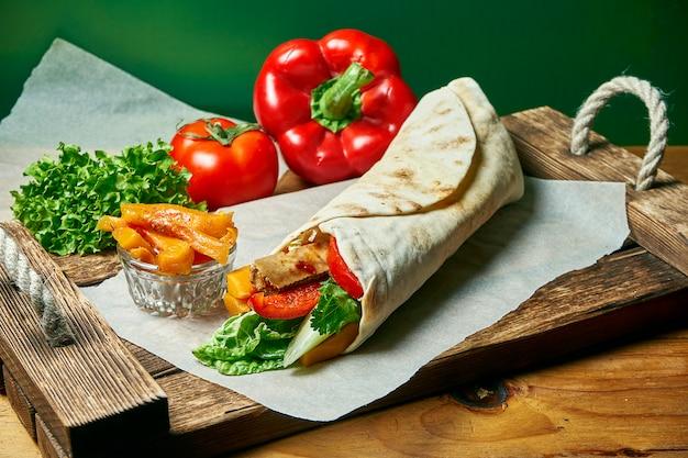 Вегетарианская шаурма ролл в лаваше с листьями салата, овощами и тыквой. вкусная, полезная и зеленая еда. веганская уличная еда