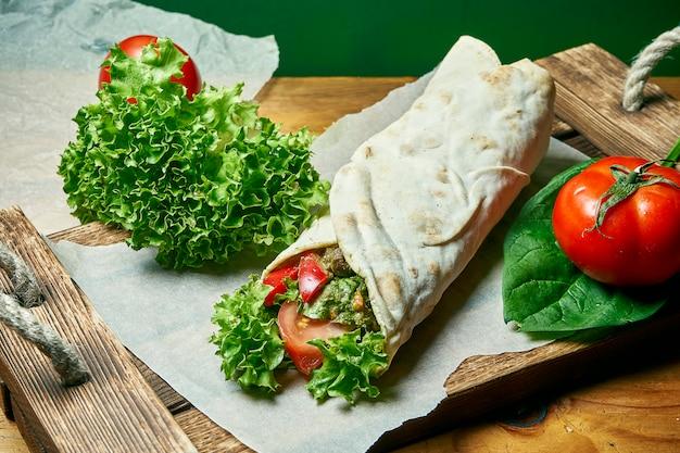 Вегетарианская шаурма ролл в лаваше с листьями салата, овощами и помидорами. вкусная, полезная и зеленая еда. веганская уличная еда