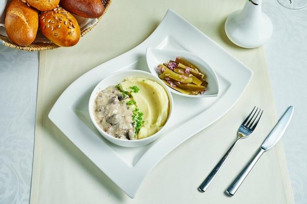 テーブルクロスに焼きたてのパンと組成の牛肉ストロガノフと繊細なマッシュポテト。レストランの料理。上面図