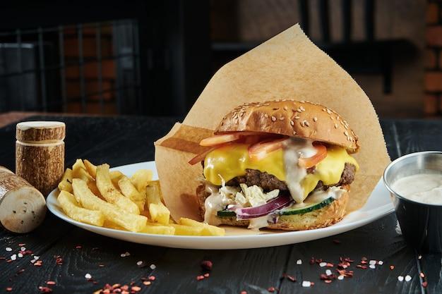 Аппетитный и сочный бургер с большой котлетой из говядины, плавленым сыром чеддер, свежими помидорами, огурцом, луком и капустой на белой тарелке с картофелем фри.