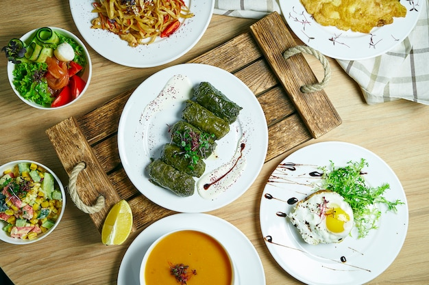 料理がたくさんあるダイニングテーブル:ドラマ、野菜サラダ、スープ、卵とデザートのビーフステーキ。トップビュー、食品フラットレイアウト