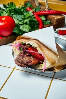 おいしい屋台の食べ物-トマト、玉ねぎとソースのピタ、白いテーブルの上の牛肉のハンバーガー。ギリシャ料理。見る。