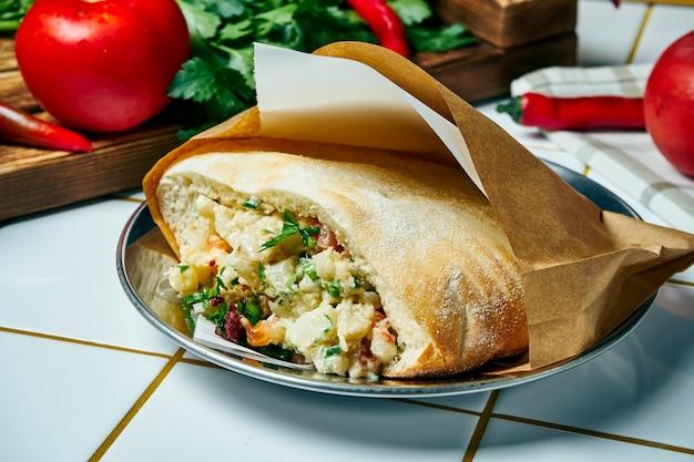 おいしいビーガンストリートフード-カリフラワー、オニオン、ソース、白いテーブルの上のピタ。ギリシャ料理。見る。