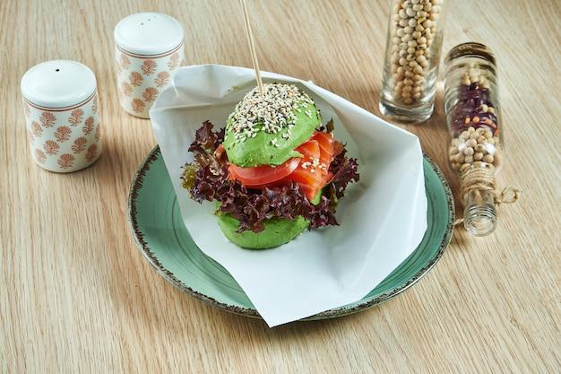 Необычный бургер из половинок авокадо, как булочки с лососем, помидорами и листьями салата. посмотреть. здоровая и зеленая еда.