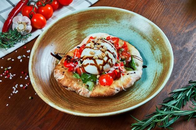 Итальянский сыр буррата с фокаччо, подается с соусом, помидорами, базиликом и орехами. ресторанное блюдо на деревянном столе. крупным планом зрения. еда плоская планировка