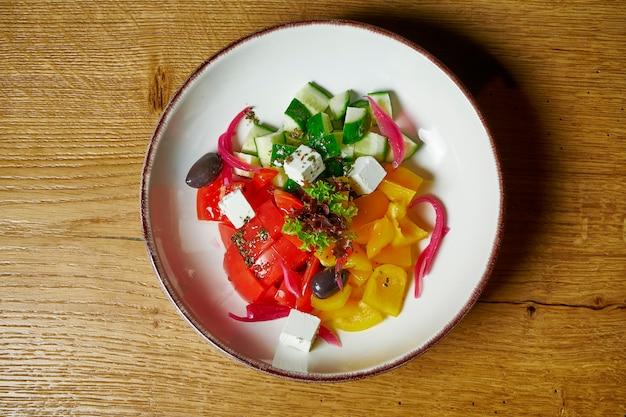 Греческий салат с помидорами, сыром фета, луком, огурцами и сладким перцем в белой миске на деревянном столе. вид сверху. здоровая пища. фитнес питание и диета