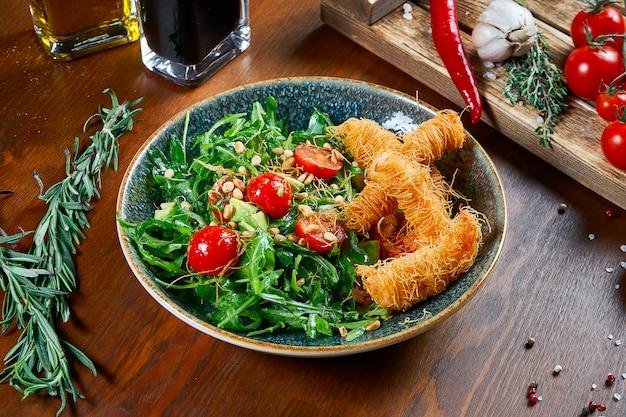 木製のテーブルのグリーンボウルにカタフィフィ生地のエビのおいしいサラダ。サラダ、ソース、トマト、ローズマリーのコンポジション。ビューを閉じます。食品フラットレイ