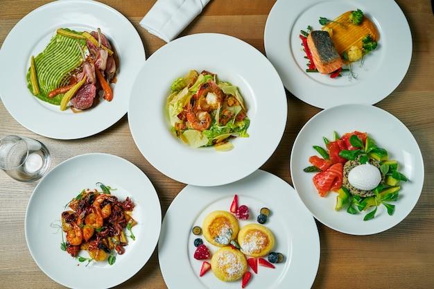 チーズケーキ、エビのサラダ、キノアとサーモンのサラダ、子羊のラック、シーフードのフライ、サーモンステーキなど、料理が豊富なダイニングテーブル。トップビューフラットレイアウト食品