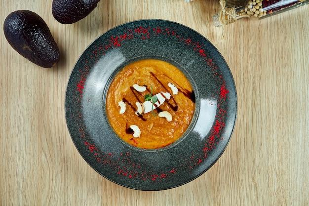 照り焼きソースと木製のテーブルに黒いボウルにカシューナッツのナスのクリームスープ。健康食品。ベジタリアンまたはフィットネス栄養。上面図