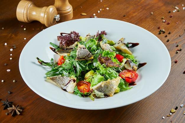 Изысканный салат с жареным сибасом, шпинатом, листьями салата, помидорами черри на деревянном столе. вкусный салат из морепродуктов. здоровая пища. диета и фитнес питание
